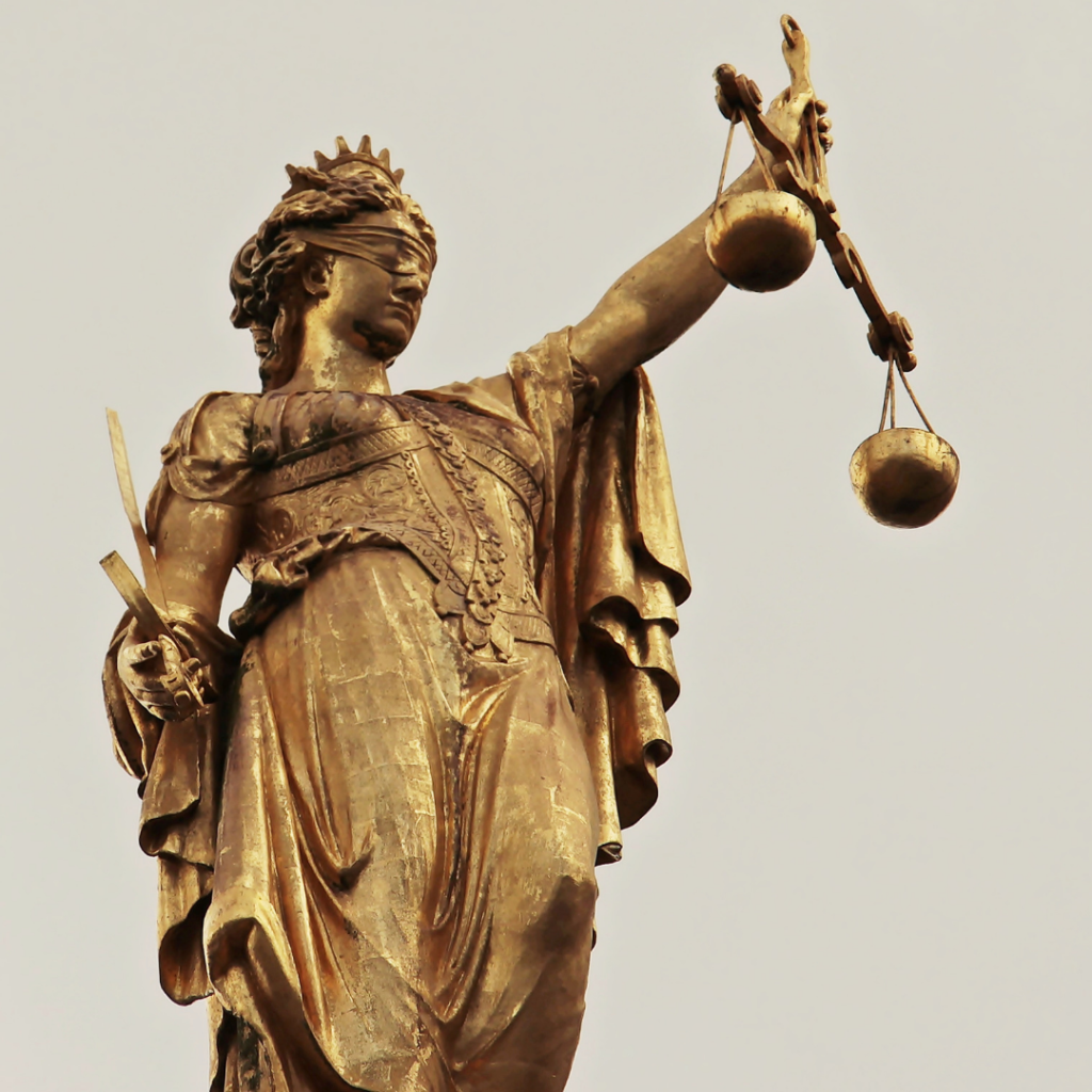Gold statue of justice, a lady in a regal robe, crown, and blindfold, holding out a set of scales