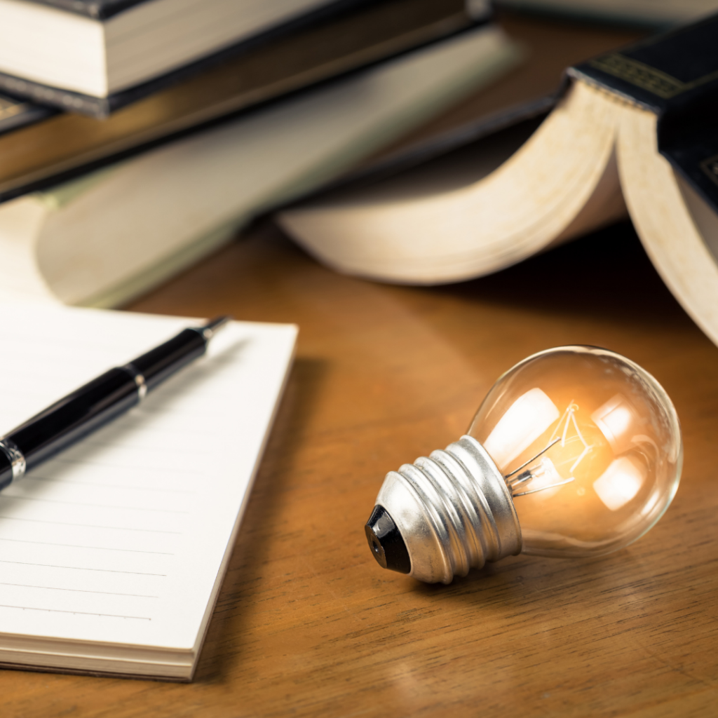 Lit lightbulb on a desk next to books and an open notepad and pen.