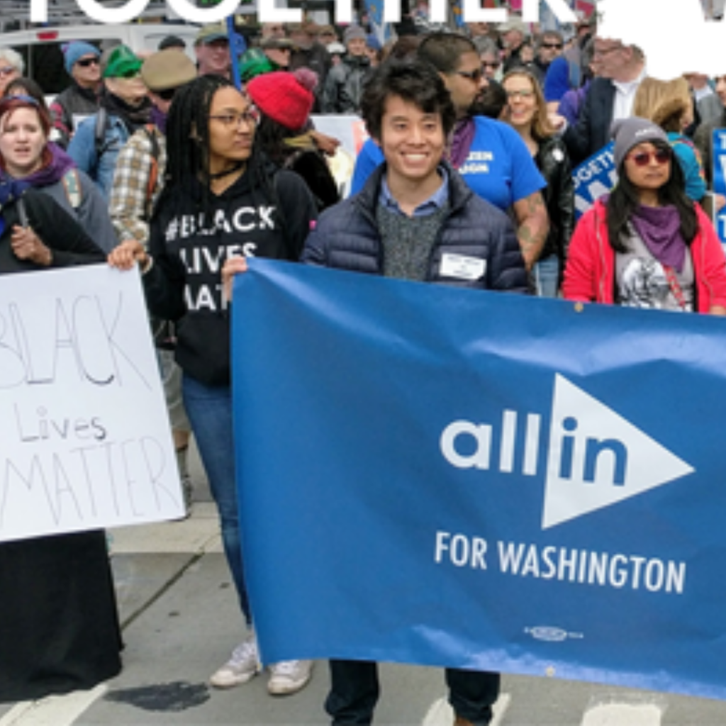 """A crowd of diverse people participates in a march, holding banners that say """"Black Lives Matter"""" and """"All In for Washington."""""""