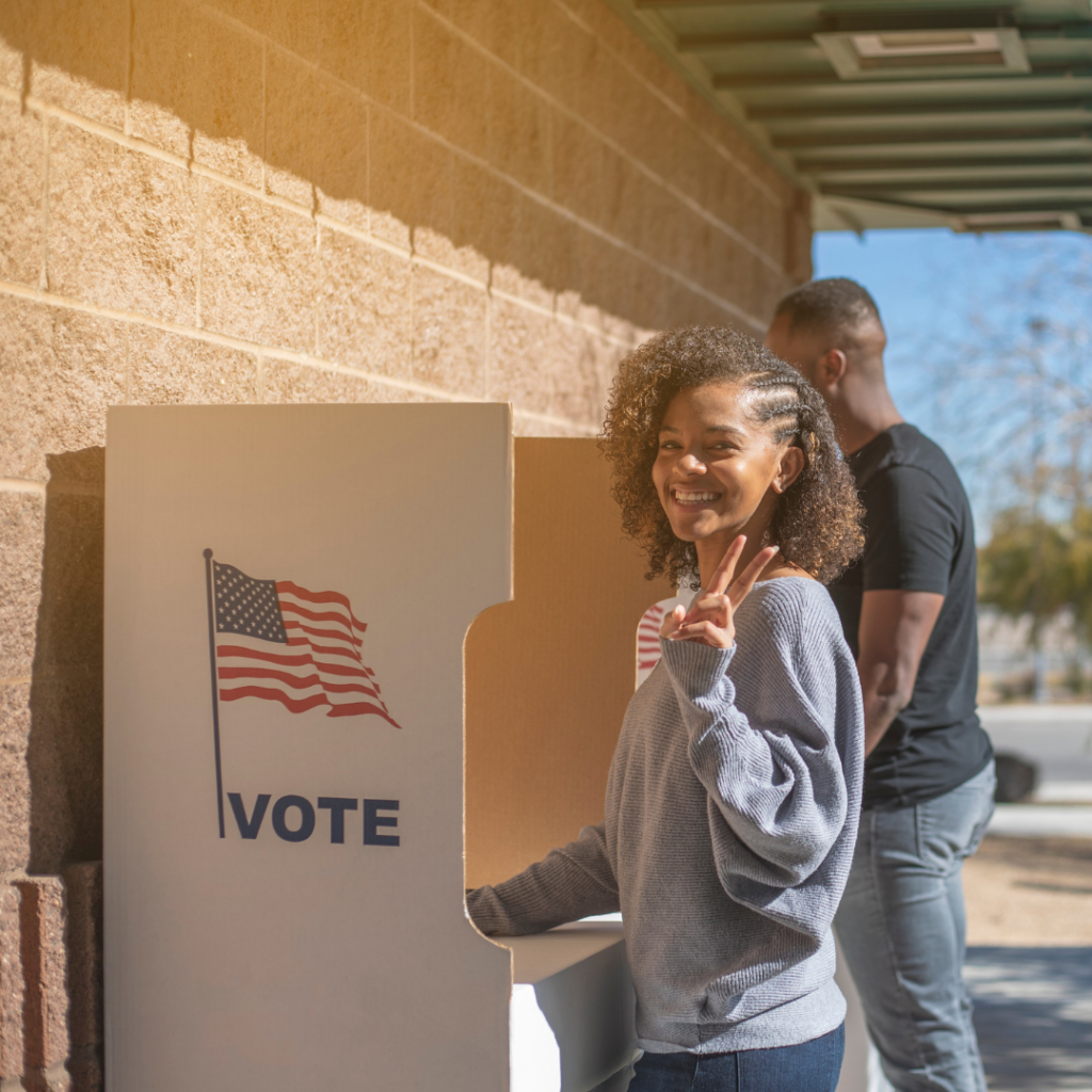 """Young African American woman making peace sign with fingers while smiling at camera, standing at a voting booth with an American flag and text that says """"VOTE"""""""